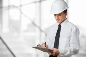 Man with Hardhat writing report